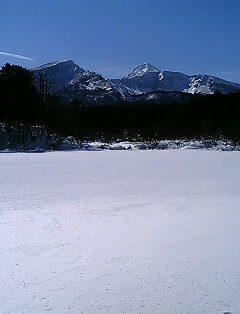 氷結した毘沙門沼と青い空